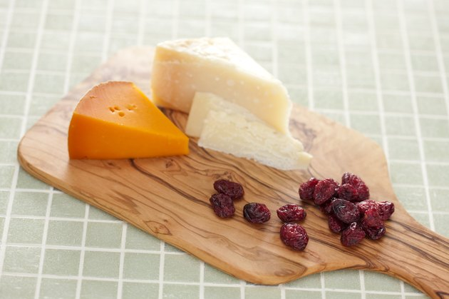 A cutting board with different kinds of cheese and dried fruit