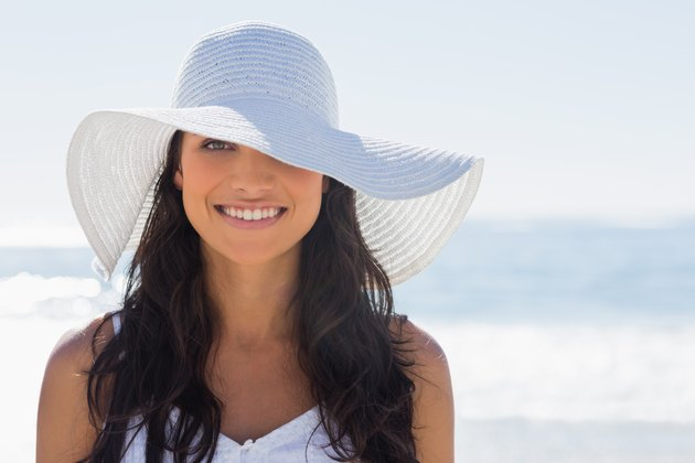 Pretty brunette in white sunhat smiling at camera
