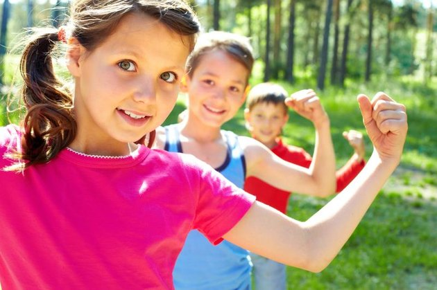 Three young children pose outdoors, flexing their biceps.