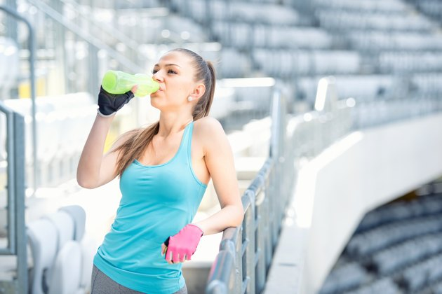 Fitness concept - young woman drinking water during workout, training
