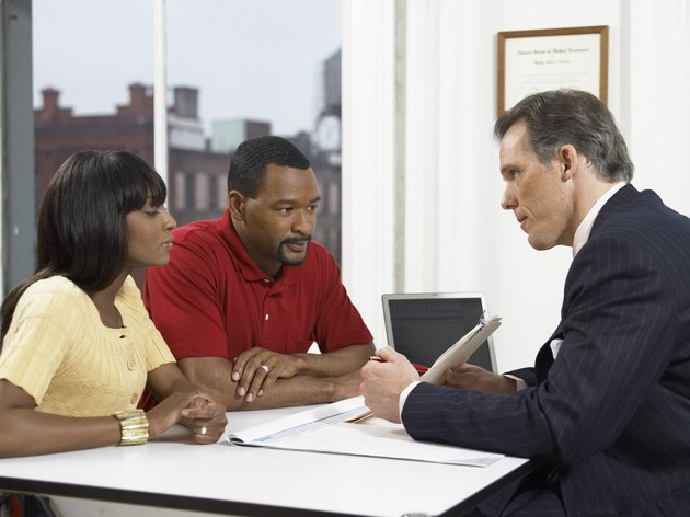 Doctor Explaining a Document to a Couple at His Clinic