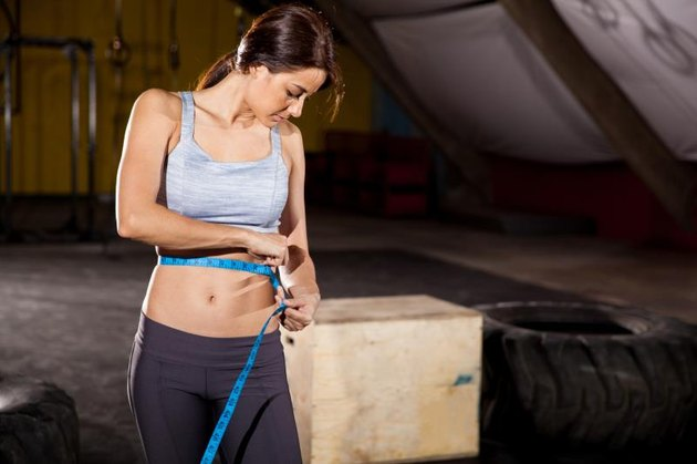 Strong young woman measuring her waist with tape at a cross-training gym