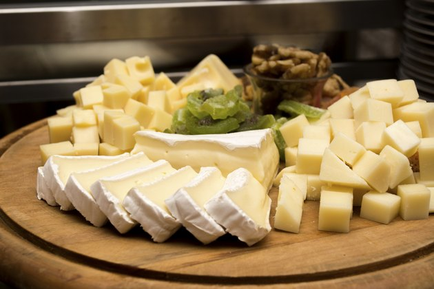 Assorted cheese on a wooden board under warm light