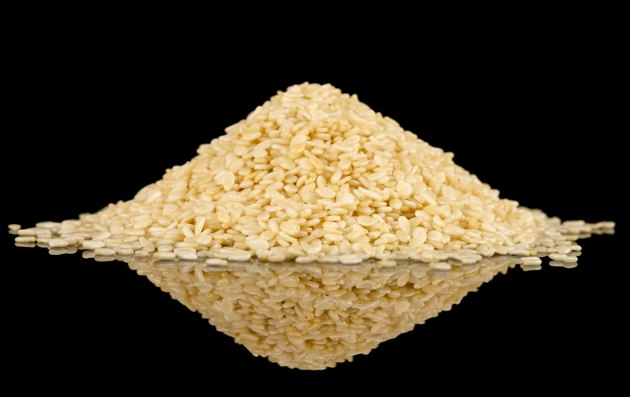 White sesame seeds on black reflective surface