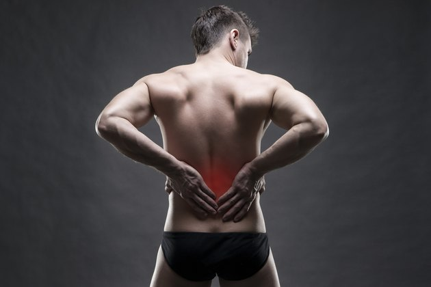 Kidney pain. Man with backache. Handsome muscular bodybuilder posing on gray background with red dot