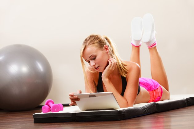 Fit woman lying on floor with tablet pc
