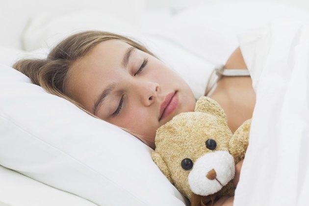 Cheerful girl sleeping with her teddy bear