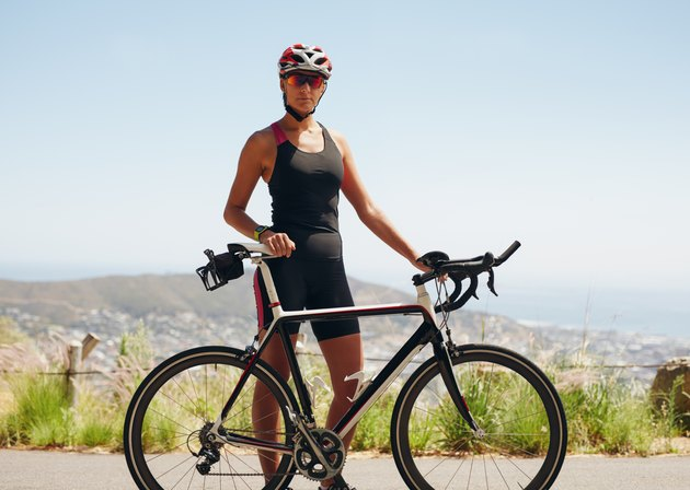 Confident female cyclist standing with her bicycle