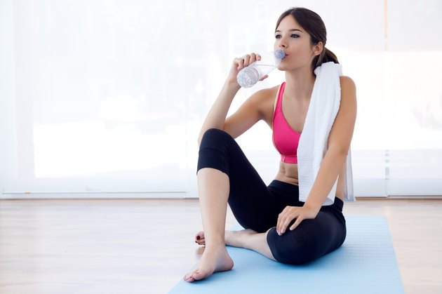 Beautiful young woman drinking water after a workout at home.