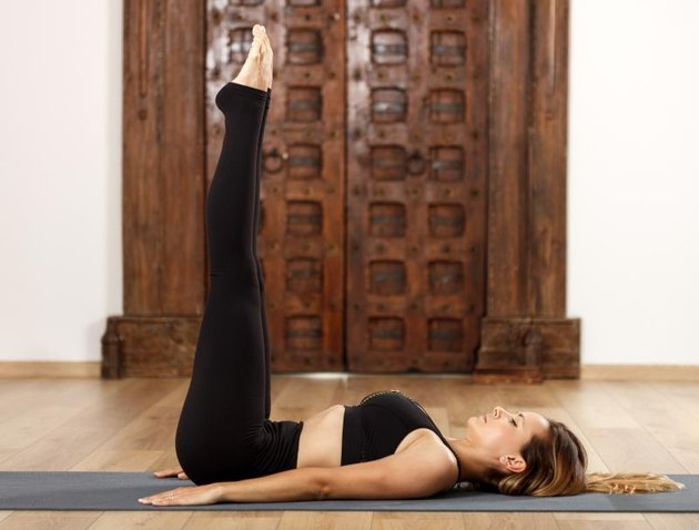 Woman yoga trainer in viparita karani (leg to wall) pose