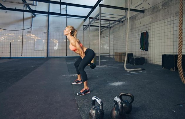 Young fitness female exercise with kettle bell. Caucasian woman doing gym workout at gym.