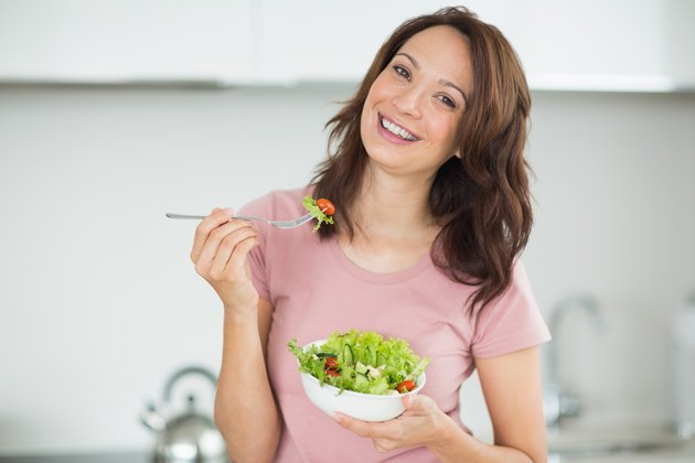 Portrait of smiling woman with a bowl of salad in kitchen