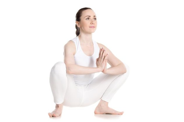 Sporty smiling beautiful young woman in white sportswear sitting in squat, Garland Pose, Malasana with hands in Namaste, studio full length shot on white background, three-quarters view, isolated