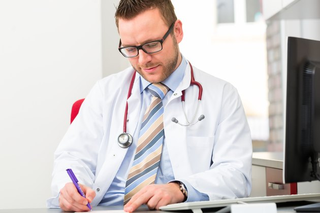 Young doctor writing medical prescription
