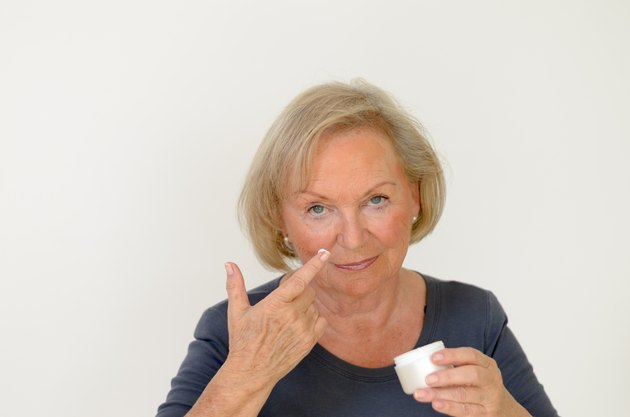 Attractive middle-aged woman applying creme