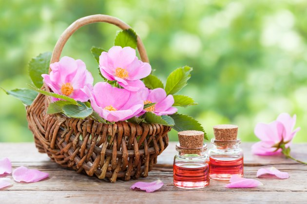 Basket with pink rose hip flowers and bottles of oil