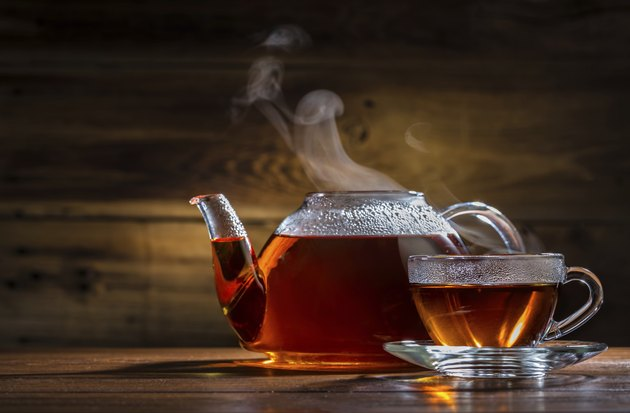 glass teapot and mug on the wooden background