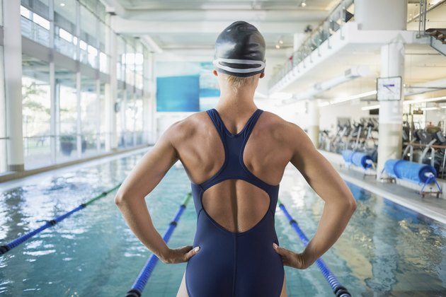 Fit female swimmer by pool at leisure center