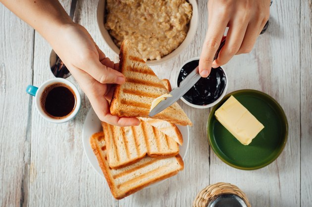 Man hands eating toast for breakfast
