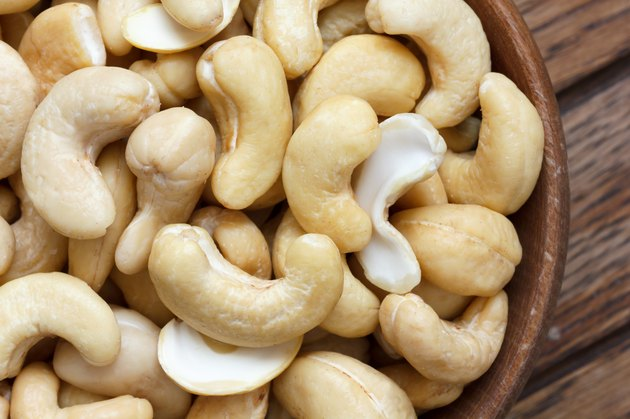 Wooden bowl of cashew nuts from above. On dark wood.