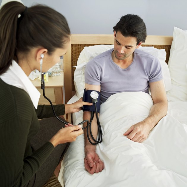 woman checking the blood pressure of male patient