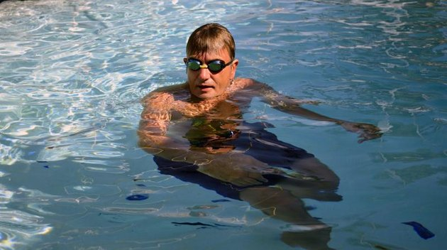 Man treading water in swimming pool wearing goggles.