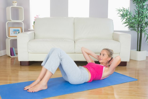 Sporty focused blonde doing sit ups