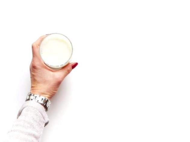 Cropped Hand Holding Glass of soylent Against White Background