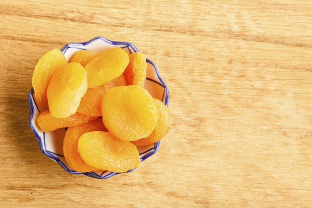 Bowl of dried apricots on wooden table background.