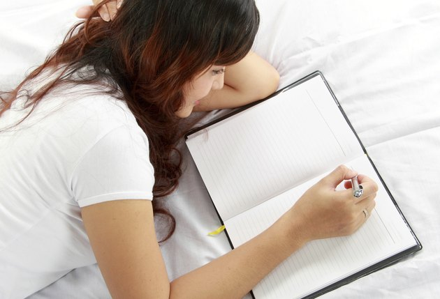 girl writing book on the bed