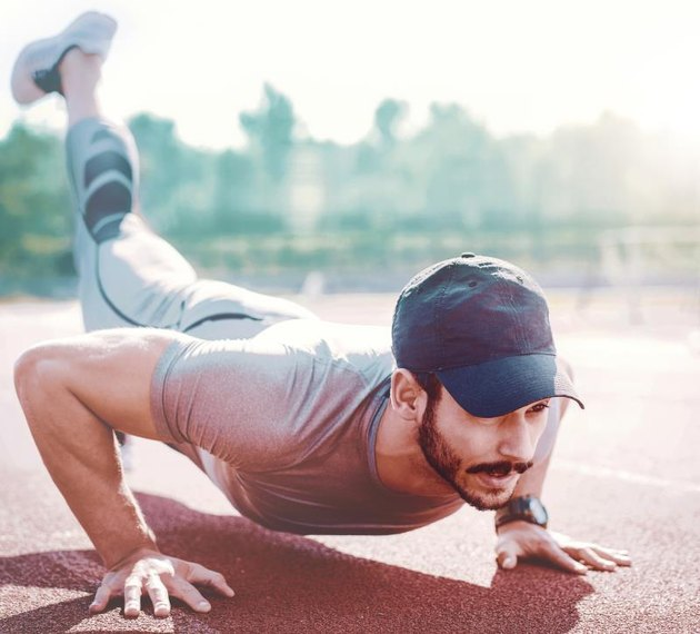 Picture of a young athletic man doing push ups outdoors, fitness and exercising in the park. Sport concept