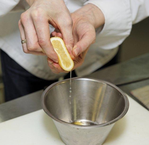 Chef is adding lemon juice in sauce
