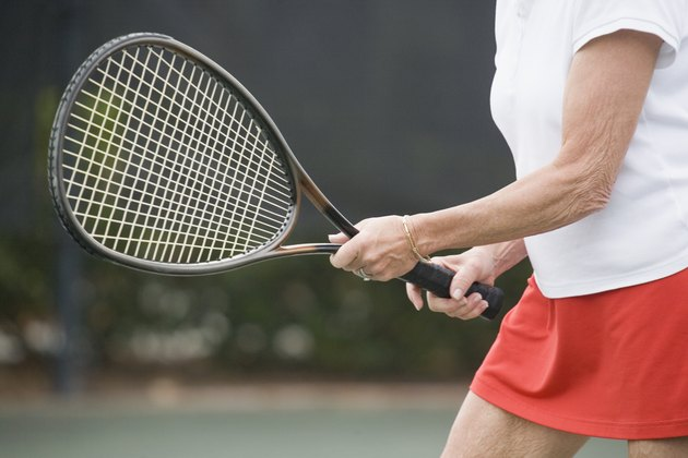 Mid section view of a senior woman playing tennis