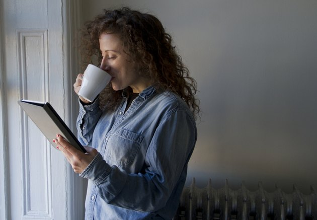 Traveller Stood At Window With Coffee Reading iPad