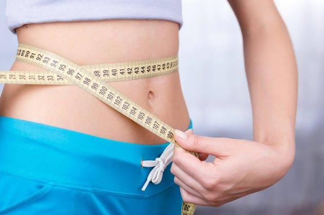 Woman measuring waist line