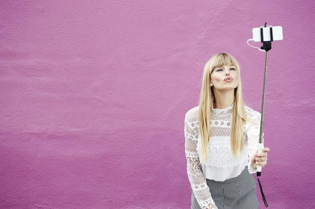 Blond beautiful blogger kissing for selfie against pink background