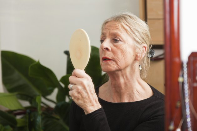 Good looking senior woman doing make-up in front of mirror.