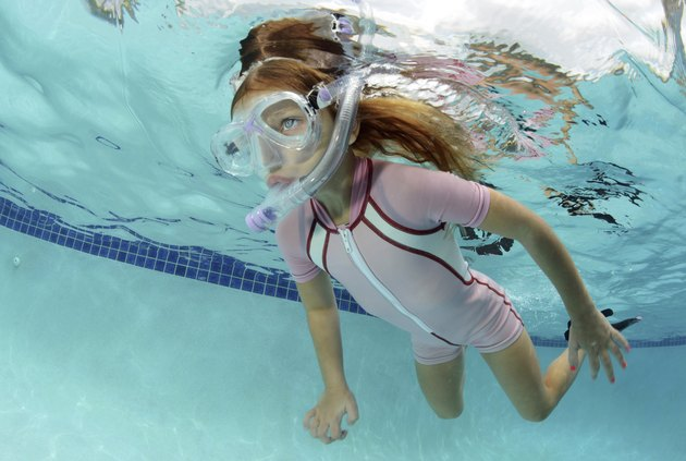 child swimming underwater in pool
