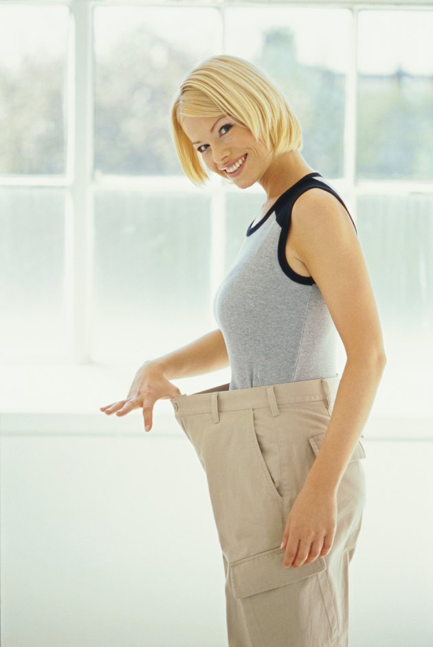 Side view of a satisfied woman stretching the waistband of her pants