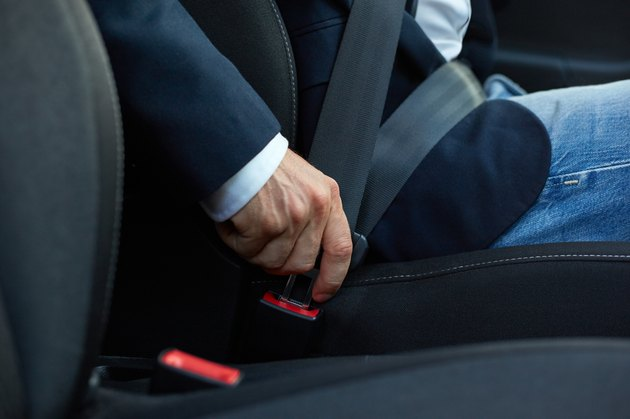 Driver fastens his seat belt
