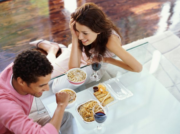 high angle view of a young couple sitting on a dining table and eating their food