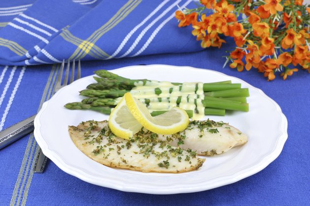 Healthy, fresh tilapia fillets with asparagus and Hollandaise sa