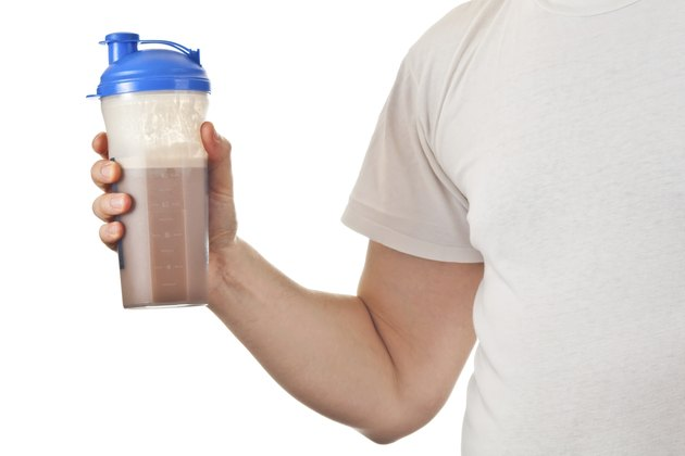 Man holding his post workout chocolate whey protein shake