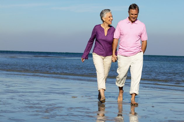 Elderly couple holding hands walking on the beach smiling
