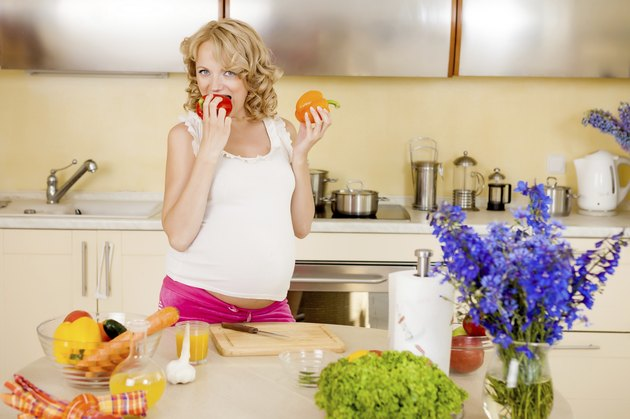 Pregnant woman prepares vegetable salad at home