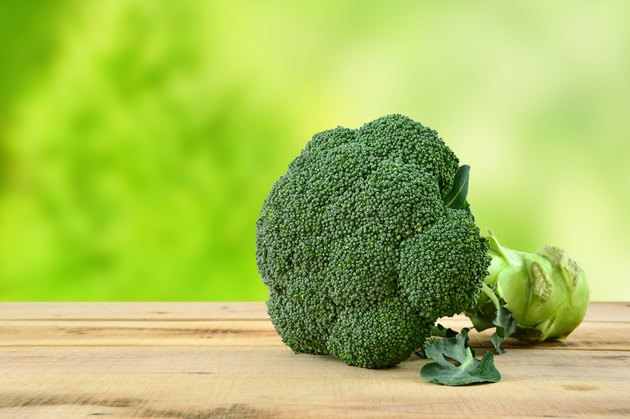 Broccoli on wooden table and green background.