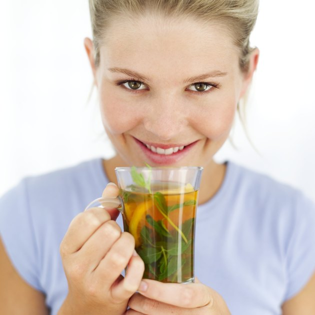 Close-up of a woman holding a cup of herbal tea