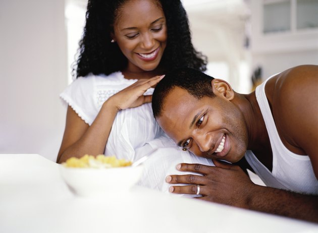 close-up of a man resting his head on his pregnant wife's stomach; smiling