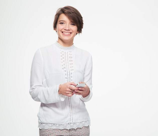Cheerful cute lovely young woman holding and using cell phone