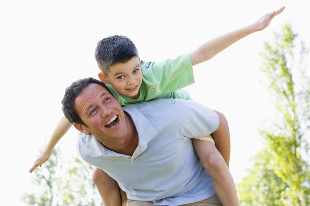 Man giving young boy piggyback ride outdoors